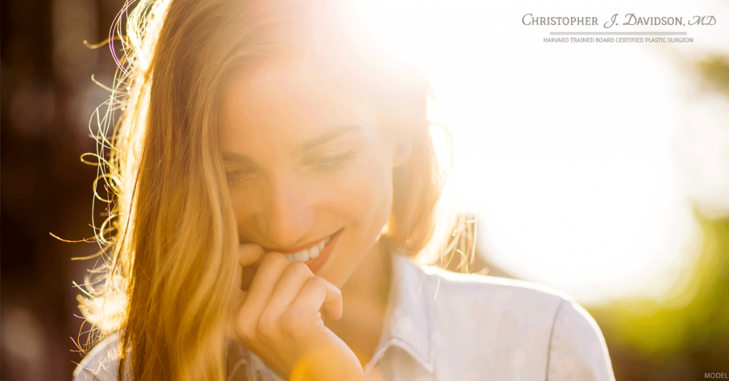 Young woman smiling with hand on her mouth looking down illuminated by sun behind her