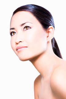 Young asian woman with bare shoulders looking up and with hair pulled behind ears