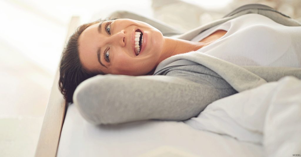 Woman wearing sweat jacket and t shirt lying on her back smiling and looking left.