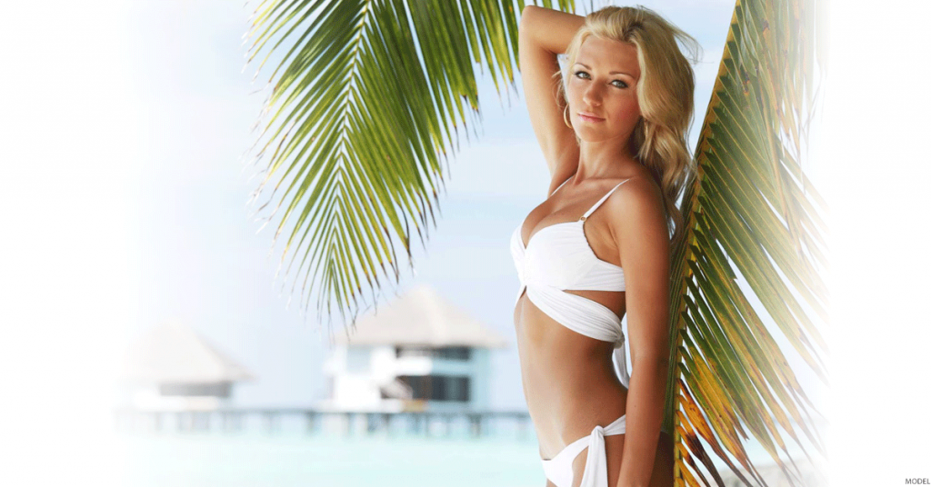 Blonde woman with beautiful body in white bikini standing under palm tree.