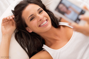 Attractive woman in white tank tap smiling