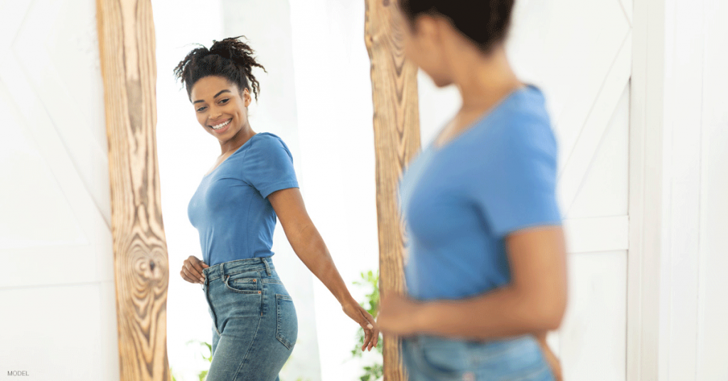 Woman in Boston, MA admiring her tummy tuck results in the mirror